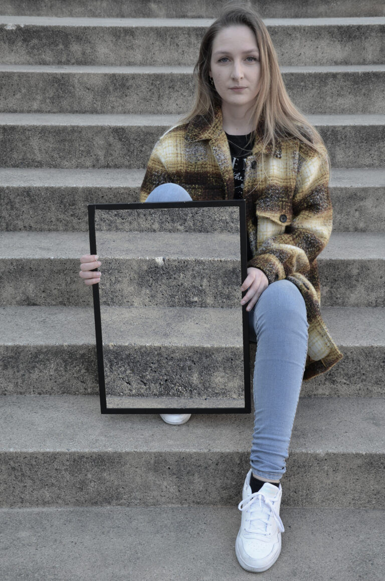 Eine Frau mit langen blonden Haaren sitzt mit angezogenem rechten Bein auf einer Treppe und schaut in die Kamera. In den Händen hält sie hochkant einen Rahmen, in dem die Treppe zu sehen ist, die sich hinter ihr befindet. Dadurch scheint es, als ob ihr rechtes Bein und Teile ihres rechten Oberkörpers unsichtbar werden.