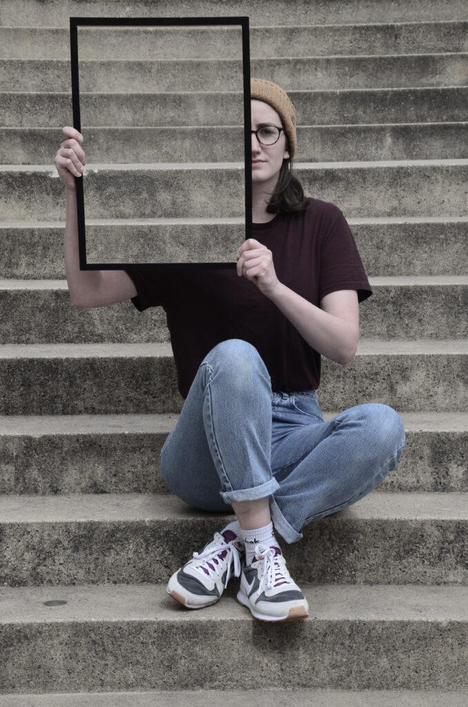 Eine Frau mit dunklem Haar, Brille und Mütze sitzt auf einer Treppe und schaut in die Kamera. In den Händen hält sie hochkant einen Rahmen, in dem die Treppe zu sehen ist, die sich hinter ihr befindet. Dadurch scheint es, als ob die rechte Seite ihres Kopfes und ein Teil ihres Oberkörpers unsichtbar werden.