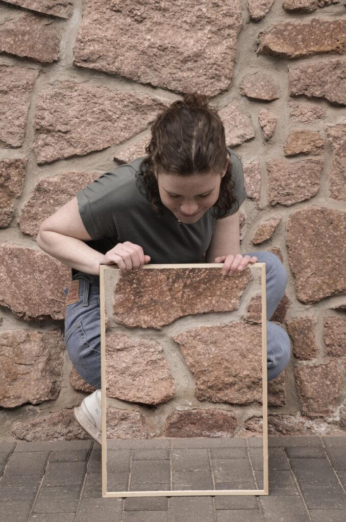 Eine Frau mit dunklen, zusammengebundenen Locken kniet seitlich vor einer Natursteinwand und schaut nach unten. Vor ihr steht hochkant ein Rahmen, auf den sie beide Hände stützt und in dem die Natursteinwand zu sehen ist, die sich hinter ihr befindet. Dadurch scheint es, als ob ihre Körpermitte sowie ein Teil ihrer Beine unsichtbar werden.