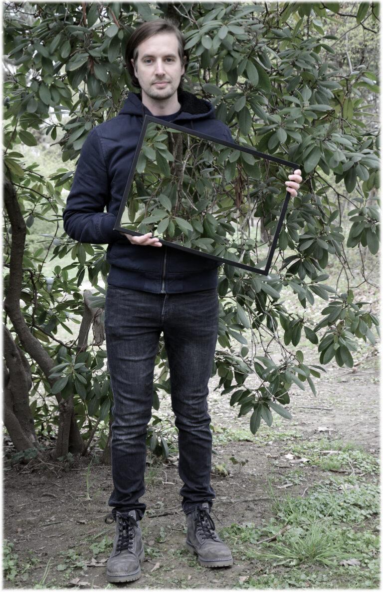 Ein Mann mit braunem Haar steht vor einem Busch und schaut in die Kamera. In den Händen hält er leicht angeschrägt einen Rahmen, in dem der Busch zu sehen ist, der sich hinter ihm befindet. Dadurch scheint es, als ob ein Teil seines Oberkörpers auf der linken Seite unsichtbar wird.