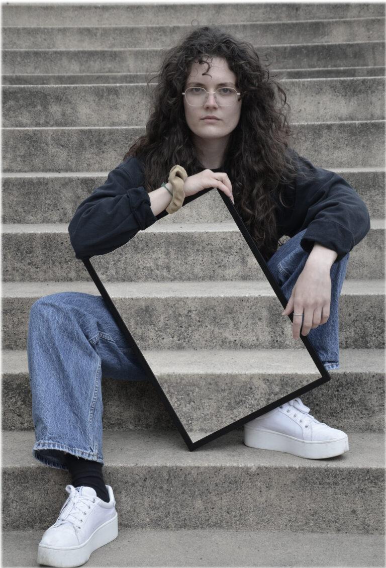 Eine Frau mit langen, dunklen Locken und Brille sitzt auf einer Treppe und schaut in die Kamera. Vor ihr steht ein angeschrägter Rahmen, auf dem sie ihren rechten Arm stützt und in dem die Treppe zu sehen ist, die sich hinter ihr befindet. Dadurch scheint es, als ob ihre Körpermitte unsichtbar wird.
