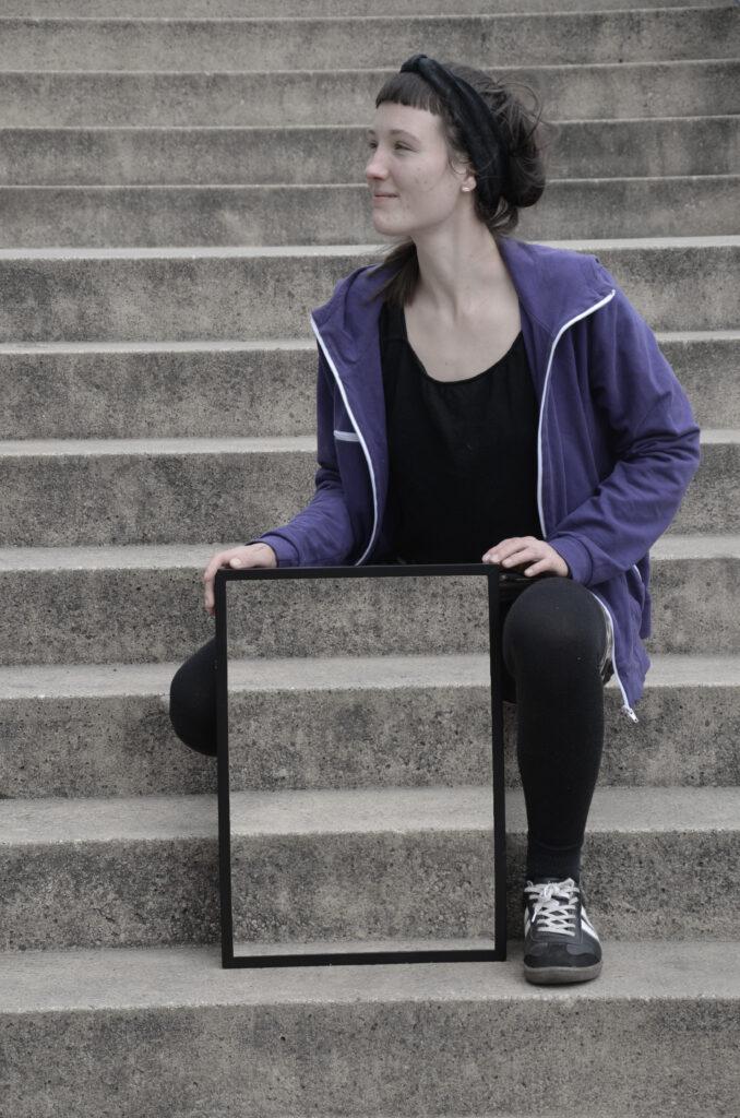 Eine Frau mit braunem Haar und Haarband sitzt auf einer Treppe und schaut nach links. Vor hier steht hochkant ein Rahmen, auf dem ihre beiden Hände liegen und in dem die Treppe zu sehen ist, die sich hinter ihr befindet. Dadurch scheint es, als ob ihr rechtes Bein unsichtbar wird.