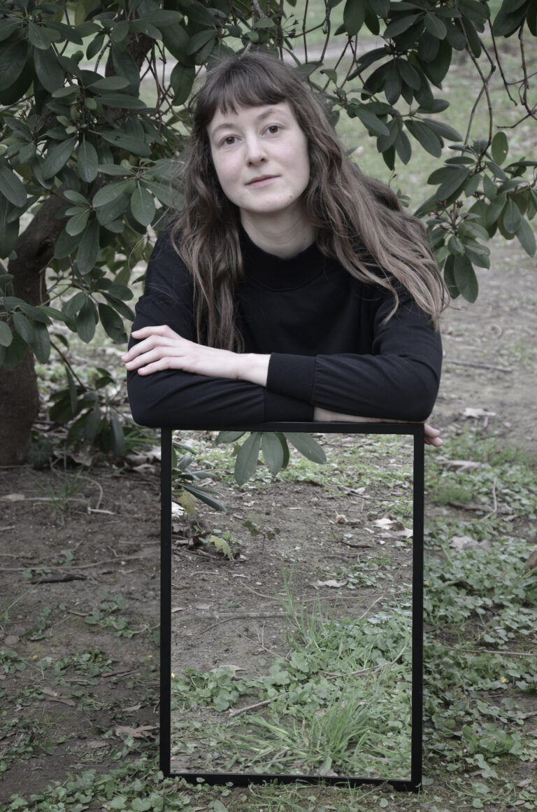 Eine Frau mit langen dunkelblonden Haaren kniet vor einem Busch und schaut in die Kamera. Sie stützt sich mit verschränkten Armen auf einen Rahmen, der hochkant vor ihr steht. In dem Rahmen ist der Busch zu sehen, der sich hinter ihr befindet. Dadurch scheint es, als ob ihr Unterkörper unsichtbar wird.