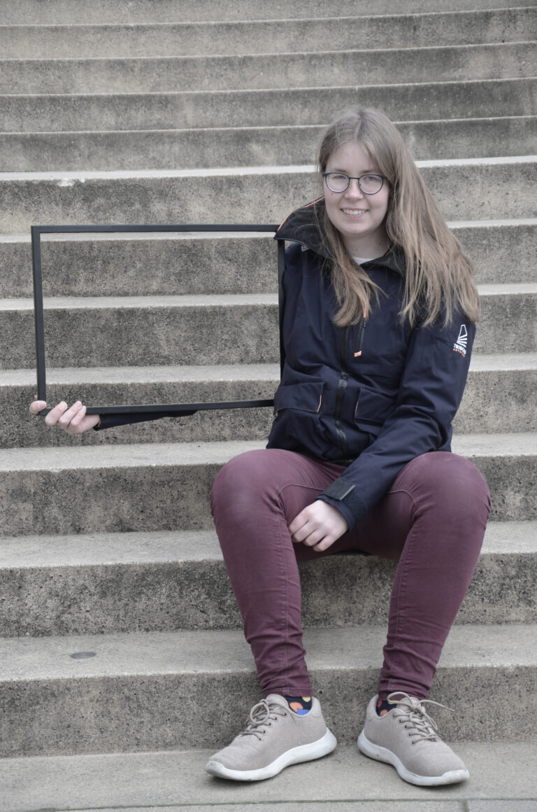 Eine Frau mit dunkelblondem, langem Haar und Brille sitzt auf einer Treppe und lächelt in die Kamera. In der rechten Hand hält sie quer einen Rahmen, in dem die Treppe zu sehen ist, die sich hinter ihr befindet. Dadurch scheint es, als ob ihr rechter Arm unsichtbar wird.