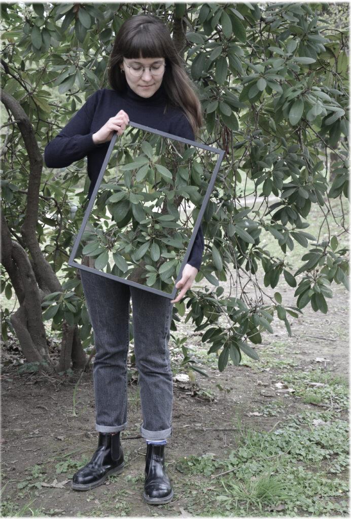 Eine Frau mit dunklem Haar und Brille steht vor einem Busch und schaut nach unten. In den Händen hält sie leicht angeschrägt einen Rahmen, in dem der Busch zu sehen ist, der sich hinter ihr befindet. Dadurch scheint es, als ob ein Teil ihrer Körpermitte und ihr linker Arm unsichtbar werden.