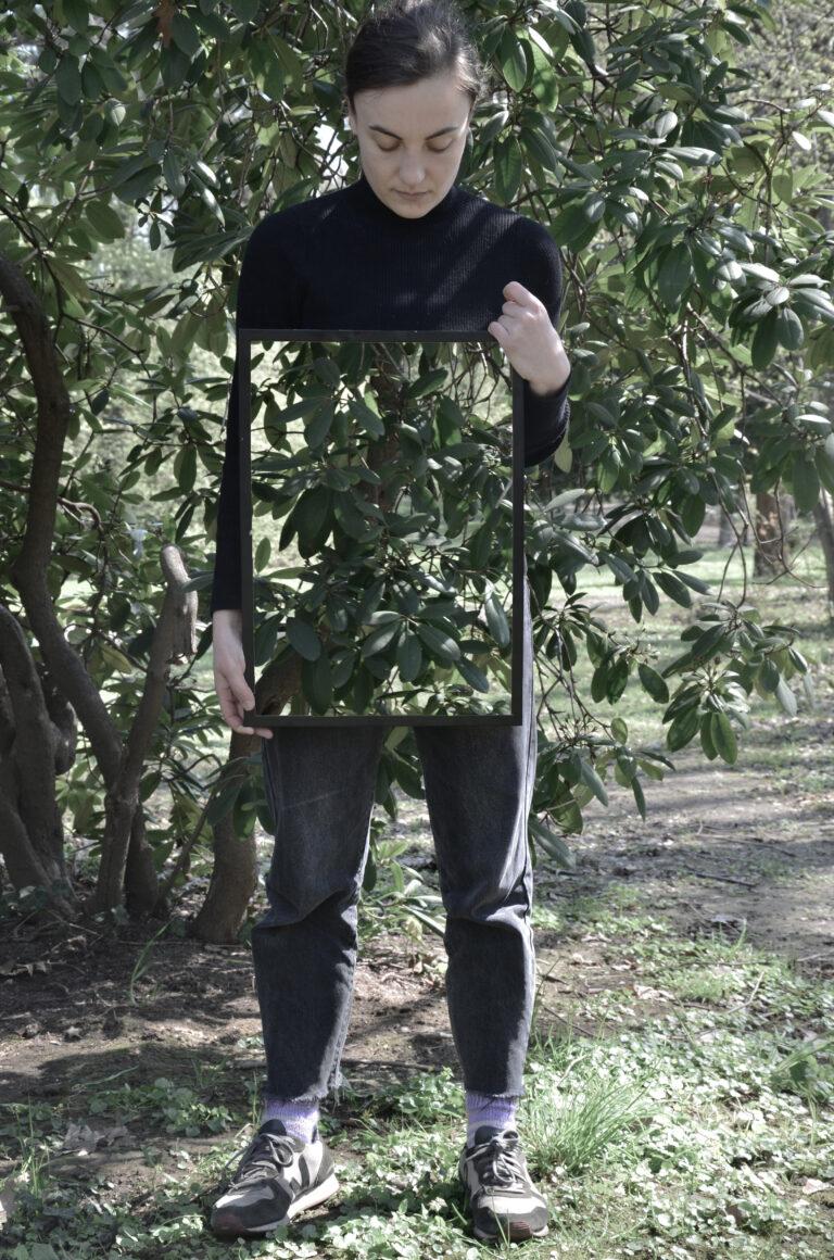 Eine Frau mit dunklen, zusammengebundenen Haaren steht vor einem Busch und schaut nach unten. In den Händen hält sie hochkant einen Rahmen, in dem der Busch zu sehen ist, der sich hinter ihr befindet. Dadurch scheint es, als ob ihre Körpermitte unsichtbar wird.