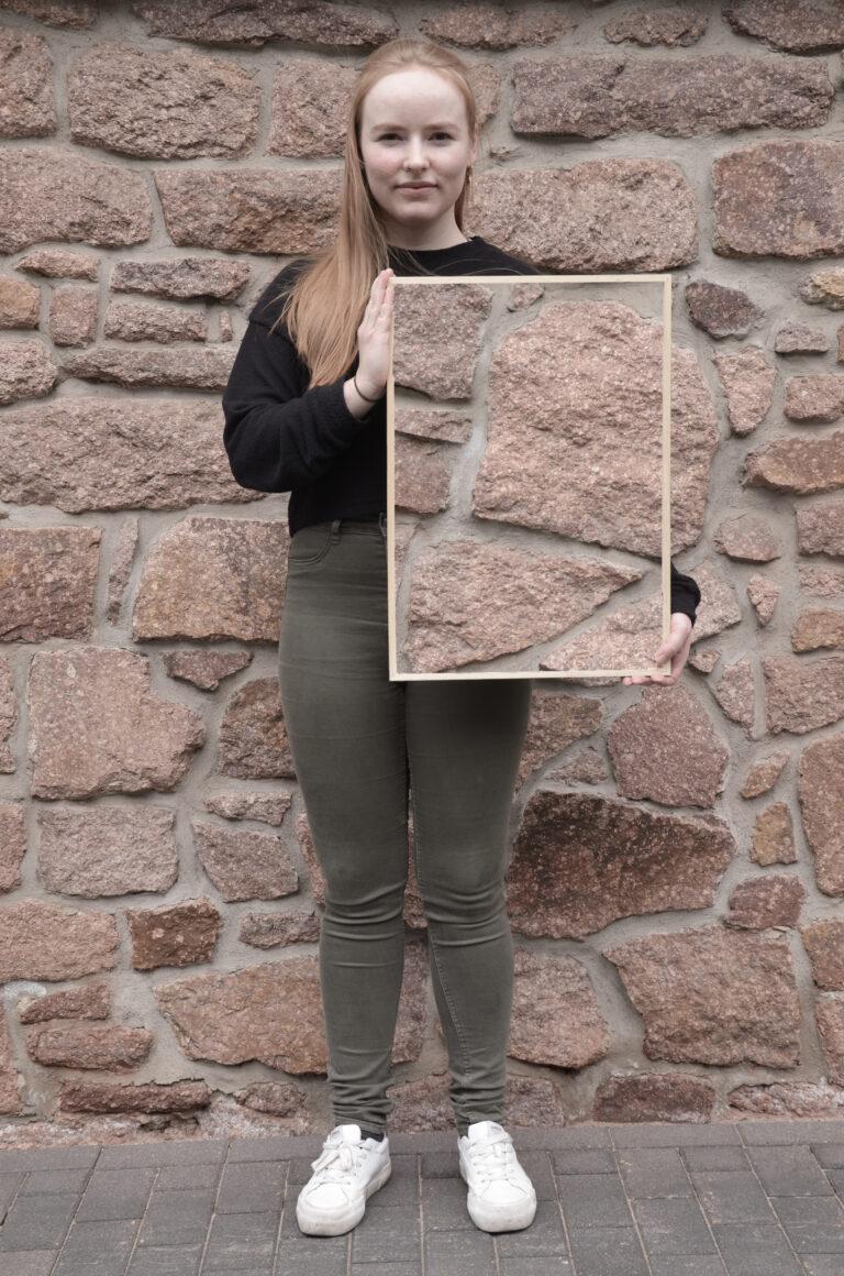 Eine Frau mit langen rötlichen Haaren steht vor einer Natursteinwand und schaut in die Kamera. In den Händen hält sie hochkant einen Rahmen, in dem die Natursteinwand zu sehen ist, die sich hinter ihr befindet. Dadurch scheint es, als ob ihre linke Körperhälfte von der Schulter bis zum Oberschenkel unsichtbar wird.