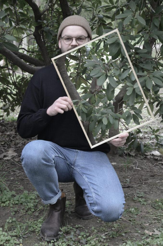 Ein Mann mit Mütze und Brille kniet vor einem Busch und schaut in die Kamera. In den Händen hält er leicht angeschrägt einen Rahmen, in dem der Busch zu sehen ist, der sich hinter ihm befindet. Dadurch scheint es, als ob ein Teil seines Gesichtes und seines Oberkörpers auf der linken Seite unsichtbar werden.