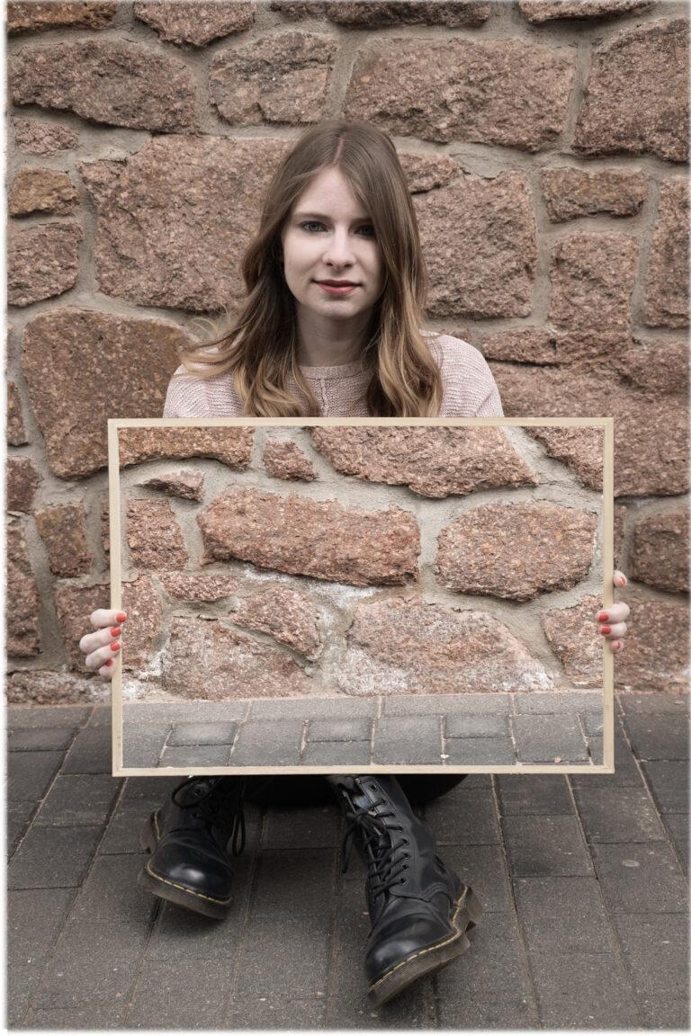 Eine blonde Frau sitzt auf dem dem Boden vor einer Natursteinwand und schaut freundlich in die Kamera. In den Händen hält sie quer einen Rahmen, in dem die Natursteinwand zu sehen ist, die sich hinter ihr befindet. Dadurch scheint es, als ob ihr Körper von den Oberarmen bis zu den Knöcheln unsichtbar wird.
