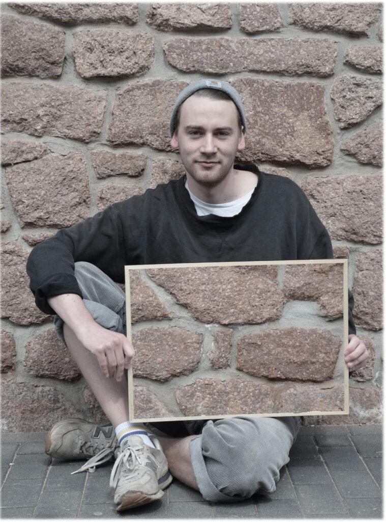 Ein Mann mit dunkelblondem Haar und einer Mütze sitzt mit angewinkeltem rechten Bein vor einer Natursteinwand und schaut in die Kamera. In den Händen hält er quer einen Rahmen, in dem die Natursteinwand zu sehen ist, die sich hinter ihm befindet. Dadurch scheint es, als ob die linke Seite seiner Körpermitte und Teile seines Beines unsichtbar werden.