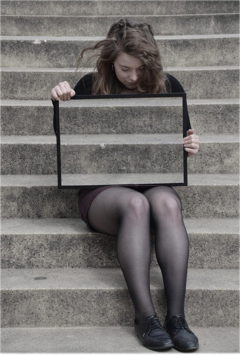 Eine dunkelblonde Frau sitzt auf einer Treppe und schaut nach unten. Ihr Oberkörper wird von einem Rahmen verdeckt, den sie quer mit beiden Händen festhält und in dem die Treppe zu sehen ist, die sich hinter ihr befindet. Dadurch scheint es, als ob ihr Oberkörper unsichtbar wird.