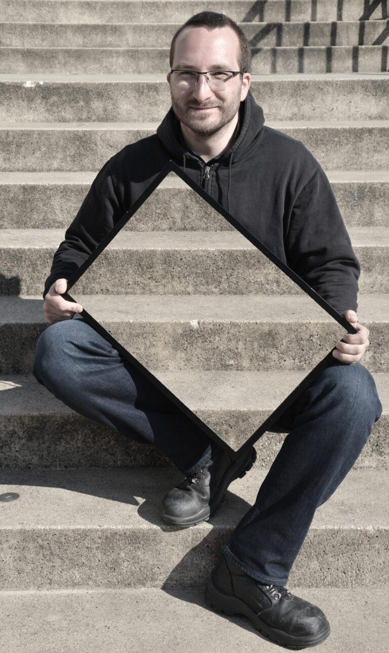 Ein Mann mit kurzen braunen Haaren und Brille sitzt auf einer Treppe und schaut in die Kamera. In den Händen hält er leicht angeschrägt einen Rahmen, in dem die Treppe zu sehen ist, die sich hinter ihm befindet. Dadurch scheint es, als ob seine Körpermitte und ein Teil seiner Beine unsichtbar werden.