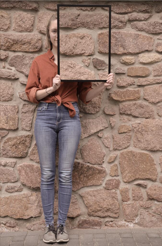 Eine Frau mit kurzem blonden Haar und Brille steht vor einer Natursteinwand und schaut in die Kamera. In den Händen hält sich hochkant einen Rahmen, in dem die Natursteinwand zu sehen ist, die sich hinter ihr befindet. Dadurch scheint es, als ob die linke Seite ihres Kopfes und ein Teil ihres Oberkörpers unsichtbar werden.