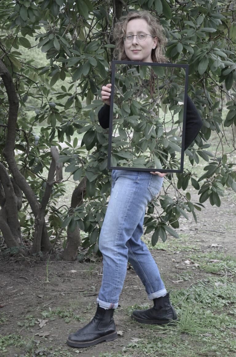 Eine Frau mit kurzen blonden Locken und Brille steht seitlich vor einem Busch und schaut in die Kamera. In den Händen hält sie hochkant einen Rahmen, in dem der Busch zu sehen ist, der sich hinter ihr befindet. Dadurch scheint es, als ob ein Teil ihrer Körpermitte und ihrer Arme unsichtbar werden.